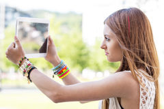 Closeup portrait of beautiful girl taking pictures wiyh tablet c Royalty Free Stock Images