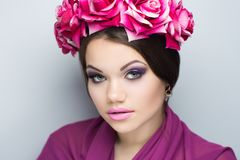 Woman pink roses. Closeup portrait of beautiful girl woman lady with volume combed hair styling. Luxury Bright makeup shiny lipstick cosmetics. New Professional Stock Image