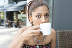 Closeup portrait of beautiful latin woman drinking coffee. Royalty Free Stock Images