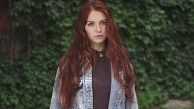 Closeup portrait of beautiful redhead girl with a sly smile. 20s. slow motion. Closeup portrait of a beautiful red-haired girl. hair fluttering in the wind. girl stock video