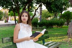 Closeup portrait of a beautiful surprised girl with wide opened eyes who is reading a book on the bench in the park. Human emotion royalty free stock image