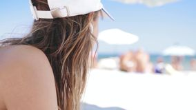 Closeup portrait of a beautiful tanned smiling woman is lying on the beach on a white sand, relaxing and listen music. Closeup portrait of a beautiful tanned stock footage