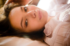 Closeup portrait of beautiful tender young lady in bed looking at camera on white background Stock Photos