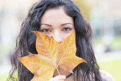 Closeup portrait of beautiful woman with autumn leaf. Royalty Free Stock Images