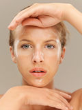 Closeup portrait beautiful woman with facial mask. Closeup beauty portrait of beautiful blonde woman with a facial mask on her skin, framing her face with her Royalty Free Stock Photos