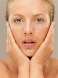 Closeup portrait beautiful woman with facial mask. Closeup beauty portrait of beautiful blonde woman with a facial mask on her face, touching her skin Stock Image