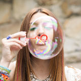 Closeup portrait of beautiful woman inflating colorful soap bubb Royalty Free Stock Image