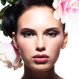 Closeup portrait of beautiful woman with pink flowers in hair Stock Images