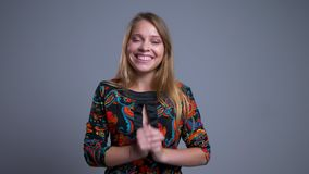 Closeup portrait of beautiful young caucasian female happily holding her arms and looking at camera with excitement.  stock footage