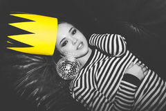Closeup portrait of beautiful young girl festive yellow paper crown on her head. Lie on leather sofa with disco ball stock images