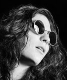 Closeup portrait of beautiful young girl in round sunglasses. Black and white Royalty Free Stock Image