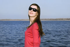 Closeup portrait of a beautiful young woman. In sunglasses over big blue sky Royalty Free Stock Photos