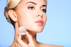 Closeup portrait of beautiful young woman applies the ice to face stock image