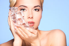 Closeup portrait of beautiful young woman applies the ice to fac Stock Photo