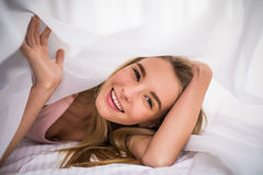 Closeup portrait of a beautiful young woman with blonde hair and under the blanket. happy good morning. Smiling woman under a duvet in her bedroom. Closeup Stock Photography