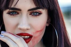 Closeup portrait of beautiful young woman with clean fresh skin touched her face and smear lipstick. outdoors stock photo