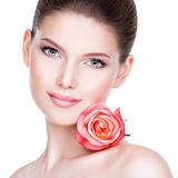 Closeup portrait of beautiful young woman with flower near face. Closeup portrait of beautiful young woman with healthy skin and flower near face - isolated on royalty free stock image