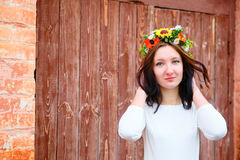 Closeup portrait of beautiful young woman with flower wreath on her head near the wooden door Stock Image