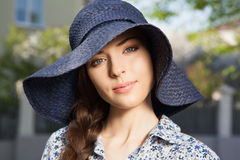 Closeup portrait of girl with braid in hat. Closeup portrait of a beautiful young woman in a hat and braid hairdo, looking at camera, outdoors Royalty Free Stock Images