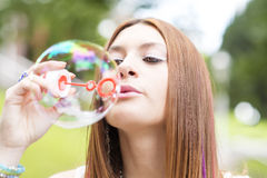 Closeup portrait of beautiful young woman inflating colorful soa Stock Photo