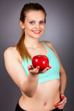 Closeup portrait of a beautiful young woman showing a red apple Stock Photography