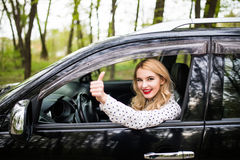 Closeup portrait of a beautiful young woman with thumbs up in her new car Royalty Free Stock Photography