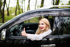 Closeup portrait of a beautiful young woman with thumbs up in her new car Stock Photography