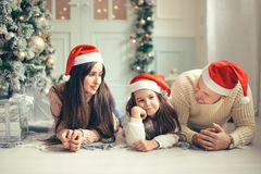 Family in Christmas Santa hats lying on bed. Mother father and baby having fun Royalty Free Stock Photos