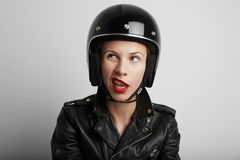 Closeup portrait of biker woman over white background, wearing stylish black sportive helmet and leather jacket. Stock Photography