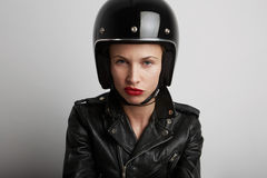 Closeup portrait of biker woman over white background, wearing stylish black sportive helmet and leather jacket. Royalty Free Stock Photos