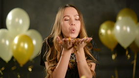 Closeup Portrait of Birthday Girl with Handful of Golden Confetti. Smiling Young Woman is Blowing on Her Hands Enjoying. Party. Black Background with Air stock video footage