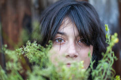 Closeup portrait of black-haired teen girl. Hidden in the greenery of the garden Royalty Free Stock Images