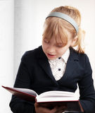 Closeup portrait of blond Caucasian schoolgirl reads textbook Royalty Free Stock Images