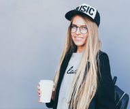 Closeup portrait of blonde girl with long haircut. Hipster, insagram style. She wears black trendy dress, glasses royalty free stock images