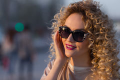 Closeup portrait of blonde girl with short hair posing on the steet on sunset background. stock images