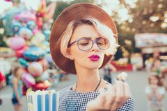 Closeup portrait of blonde girl with short haircut in amusement park on baloons background. She wears checkered dress. Closeup portrait of  blonde girl with royalty free stock images
