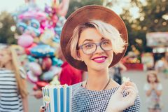 Closeup portrait of blonde girl with short haircut in amusement park on baloons background. She wears checkered dress. Closeup portrait of  blonde girl with royalty free stock photography