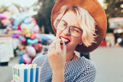 Closeup portrait of blonde girl with short haircut outdoor on baloons background. She wears checkered dress, hat. Closeup portrait of  blonde girl with short stock image