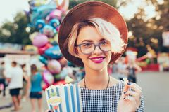 Closeup portrait of blonde girl with short haircutotdoor on baloons background. She wears checkered dress, hat, glasses. Closeup portrait of  blonde girl with stock photo