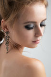 Closeup portrait of blondes with long earrings with closed eyes and silvery eyeshadows. Vertical photo on a light background Stock Photography