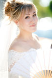 Closeup portrait of bride with fan outdoors in the sun. Stock Photos