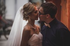 Closeup portrait of bride and groom kissing in ancient tunnel made of bricks Stock Photos