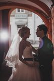 Closeup portrait of bride and groom kissing in ancient tunnel made of bricks Stock Images