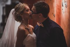 Closeup portrait of bride and groom kissing in ancient tunnel made of bricks Royalty Free Stock Image
