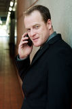 Closeup portrait of business man using cell phone. Standing inside a building Royalty Free Stock Photos