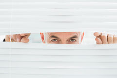 Closeup portrait of a businessman peeking through blinds Royalty Free Stock Photos