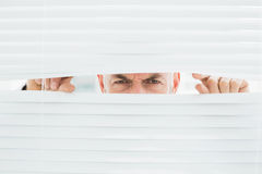 Closeup portrait of a businessman peeking through blinds Stock Photo