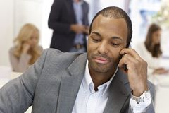 Closeup portrait of businessman on phone call. Closeup portrait of afro businessman talking on mobilephone in busy office Royalty Free Stock Image