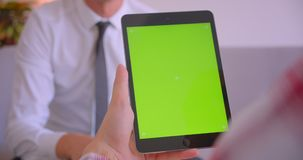 Closeup portrait of businessman talking to client holding tablet with green chroma key screen in office.  stock footage