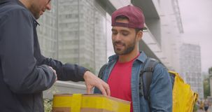 Closeup portrait of caucasian delivery man with backpack delivering order and having his customer sign in app on phone. In city outdoors stock footage